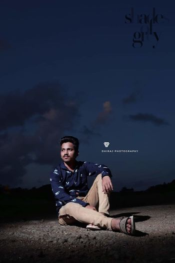 Young man looking away while sitting on land against sky at night