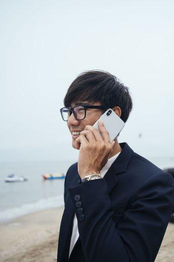 Portrait of man using mobile phone against sea