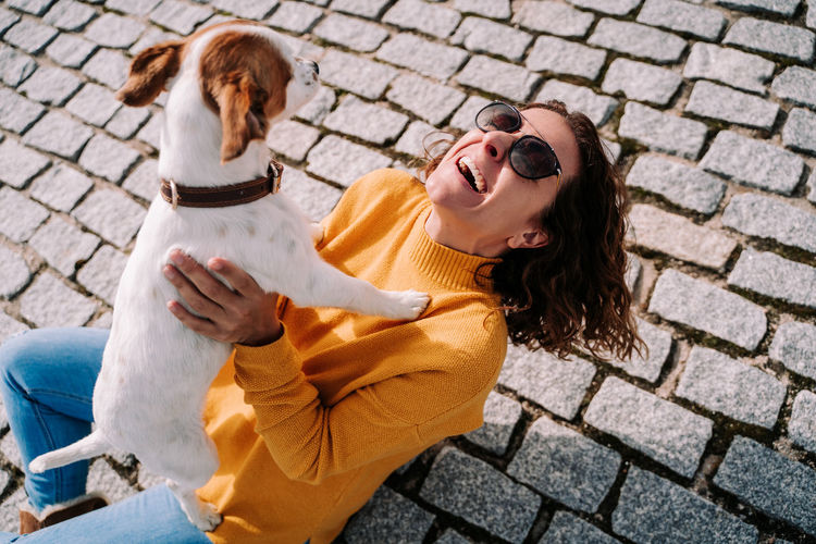 Smiling woman playing with dog outdoors