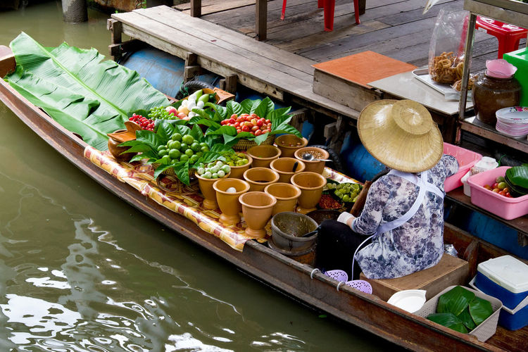 Traditional merchant in Taling Chan floating market, Bangkok, Thailand ASIA Asian  Bangkok Green Color Merchant Taling Chan Thailand Boat Colorful Floating Market Food And Drink Freshness Fruit Leaf One Person Papaya Salad Photography Small Business Traditional Travel Destinations Vegetable Water Wooden