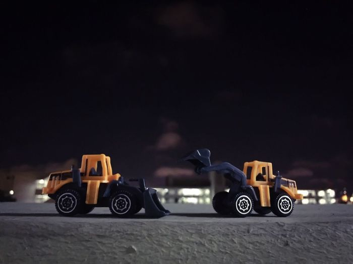 Close-up of toy earth movers on retaining wall against sky at night