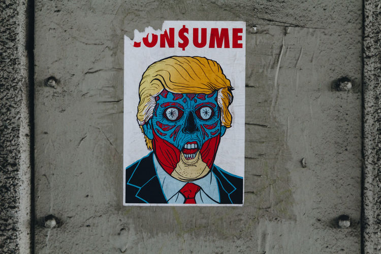 A poster of Trump likeness with the message of Consume on a steel panel underneath a bridge. - IG: @LostBoyMemoirs Streetwise Photography Streetphotography Street Photography Art And Craft Representation Human Representation Male Likeness Graffiti Propaganda Trump Politics And Government Political