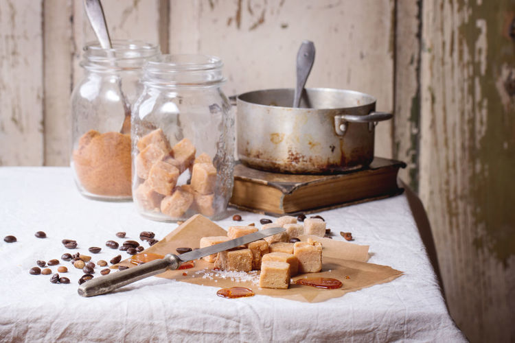 Fudge candy, coffee beans and caramel on baking paper, served over white tablecloth with vintage knife, jar of brown sugar and old pan Baking Paper Beige Brown Butterscotch Candy Caramel Confection Confectionery Creamy Cubes Dessert Food Food And Drink Fudge Glass Jar Homemade Food Mason Jar Pan Sugar Sweet Food Table Tablecloth Toffee Vintage White