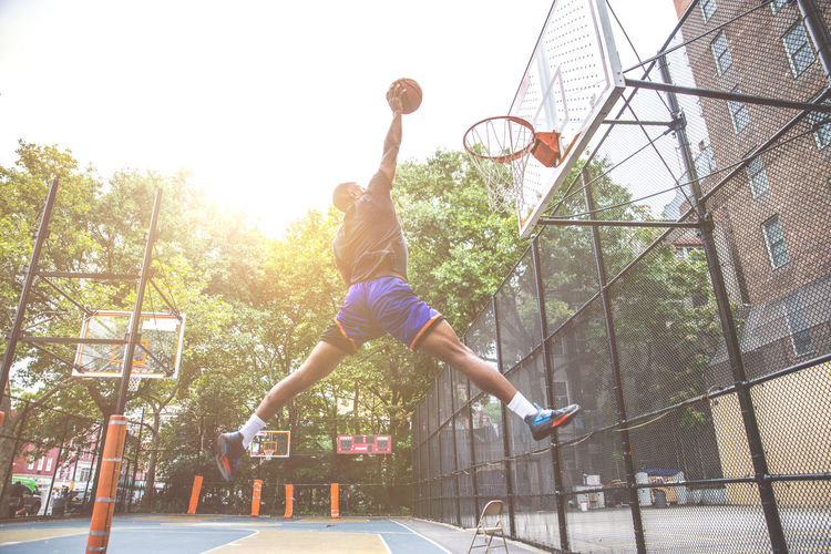 Young man playing basketball in court