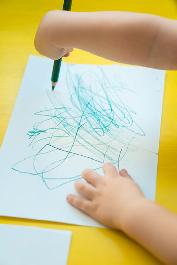 High Angle View Of Kid Scribbling On Paper At Table