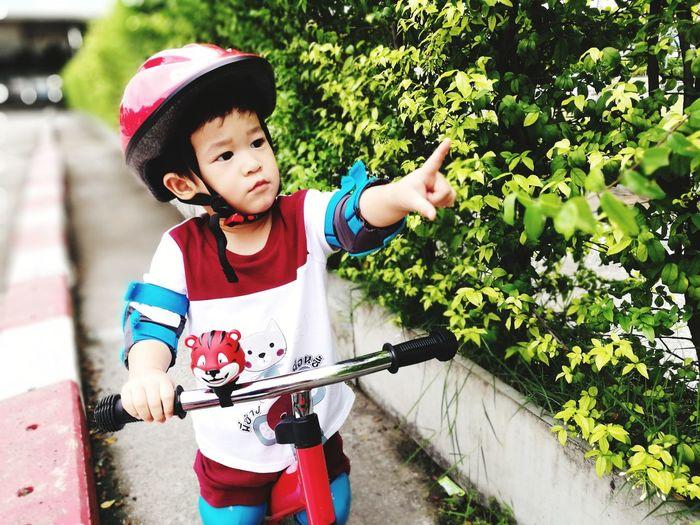 Cute boy gesturing on footpath