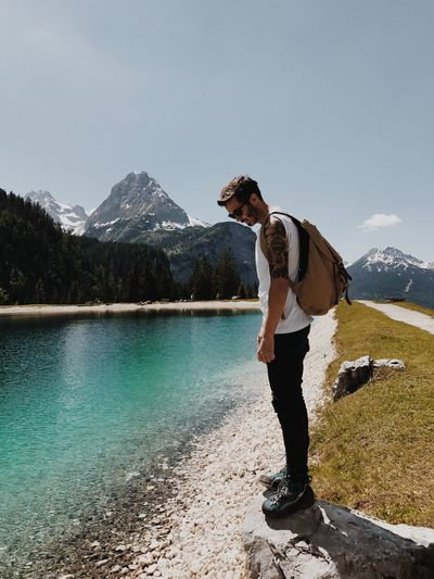Full length of young man standing by lake against mountains