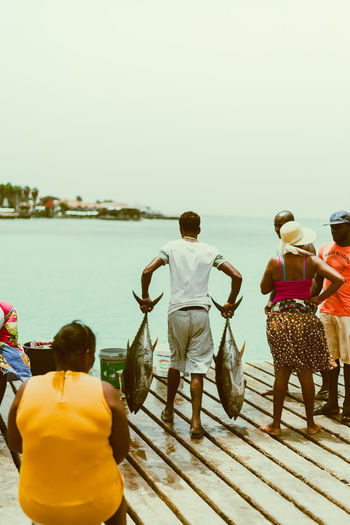 Bringing in the tuna catch on the quay in Cape Verde, Africa Cape Verde Travel Africa Clear Sky Day Fish Market Fishing Full Length Horizon Over Water Lifestyles Men Nature Outdoors Quay Real People Rear View Sea Sky Standing Tuna Vacations Water Women