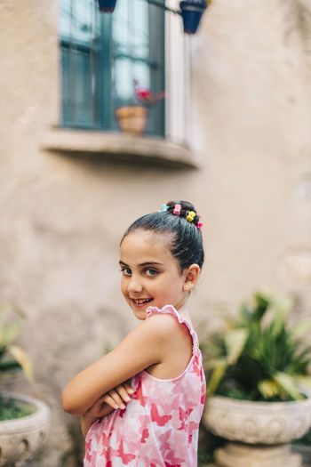 Portrait of cute smiling girl standing against wall