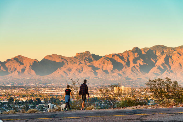 Couple hiking in Tucson with Catalina Mountains in the background Catalina Mountains  Tucson Adult Arid Climate Beauty In Nature Clear Sky Day Desert Full Length Landscape Lifestyles Men Mountain Mountain Range Nature Outdoors People Real People Rear View Road Scenics Sky Sunset Togetherness Tranquil Scene