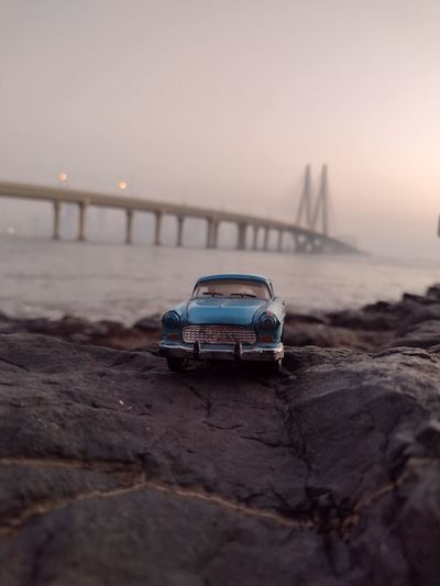 Miniature car on sea shore against sky during sunset