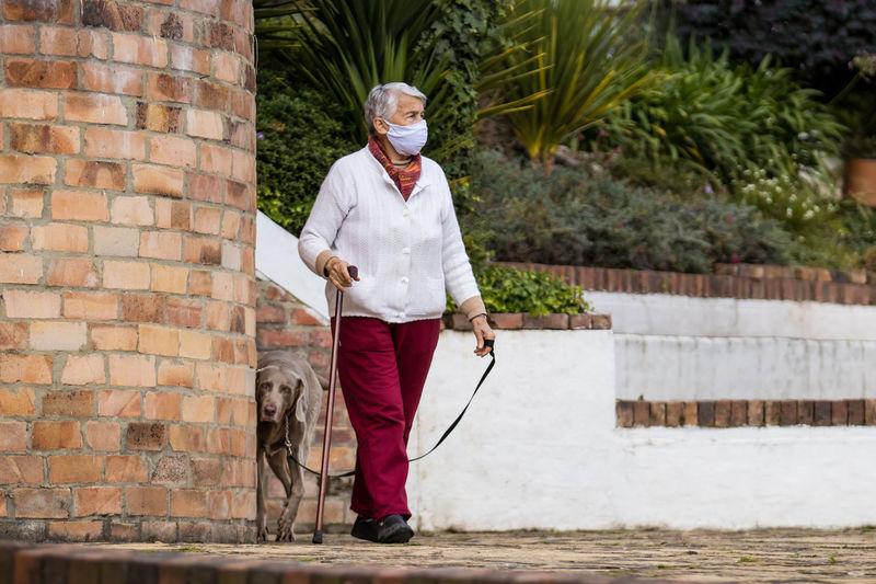Full length of senior wearing mask with dog walking outdoors