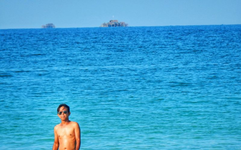 Portrait Of Shirtless Man Standing In Sea