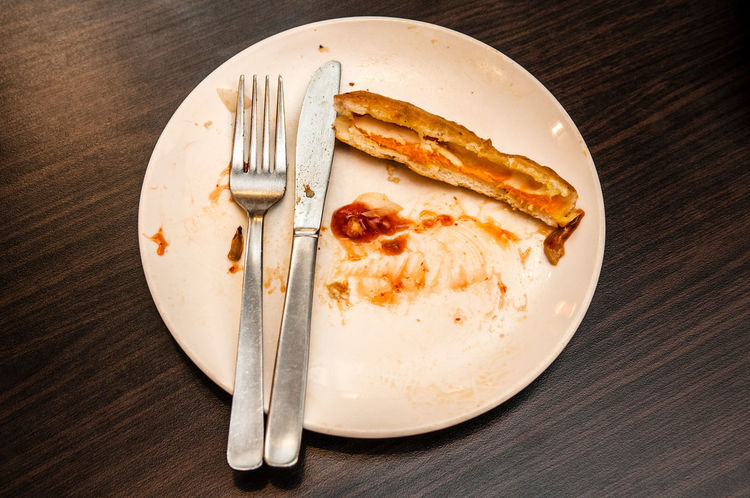 Top view of leftover food with fork and knife on plate. Dirty Dishes Food Waste Close-up Directly Above Eating Utensil Food Fork Indoors  Knife Leftovers No People Plate Still Life Top View Unfinished