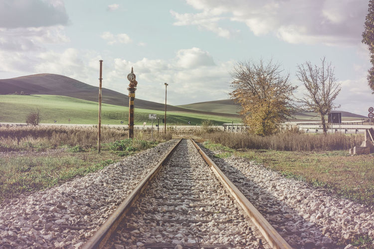 Railroad track amidst field against sky