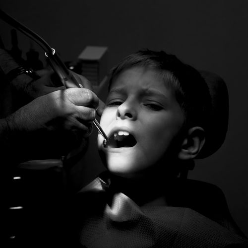 Cropped Hands Of Dentist Examining Boy