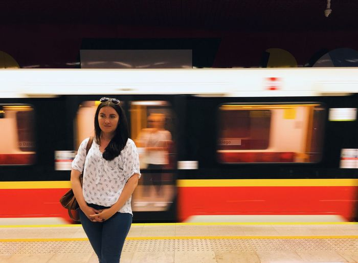 Young woman standing against blurred train at subway station