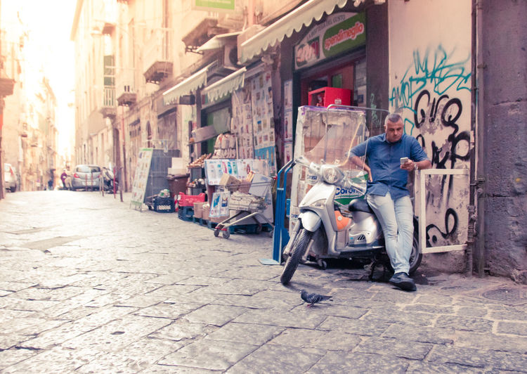 Naples Italy❤️ South Italy City Street Streetphotography Architecture Building Exterior Day Outdoors Footpath Paved Full Length One Person Sitting Graffiti Casual Clothing Creativity City Life Art And Craft Adult Men Young Adult Artist Mid Adult Alley Hairstyle Jeans Waiting Phone Alone Summer Sunny Light The Street Photographer - 2019 EyeEm Awards