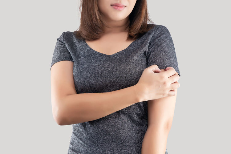 Midsection of woman standing against white background