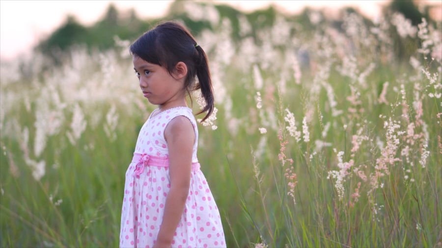 Side view of thoughtful girl standing against plants