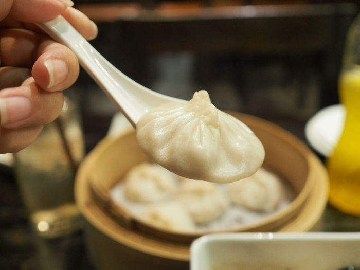 Close-up of cropped hand holding chinese dumpling on spoon