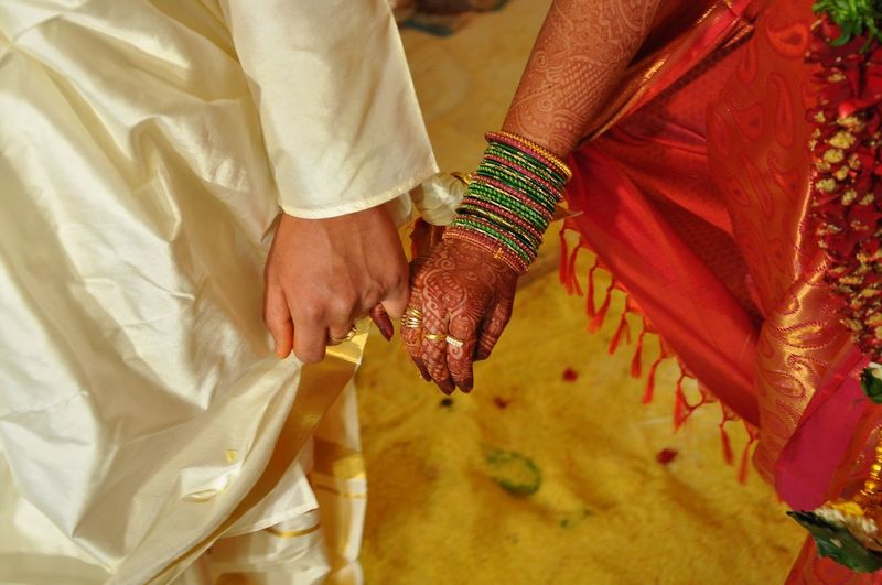 Midsection of indian bridal couple holding hands during wedding ceremony