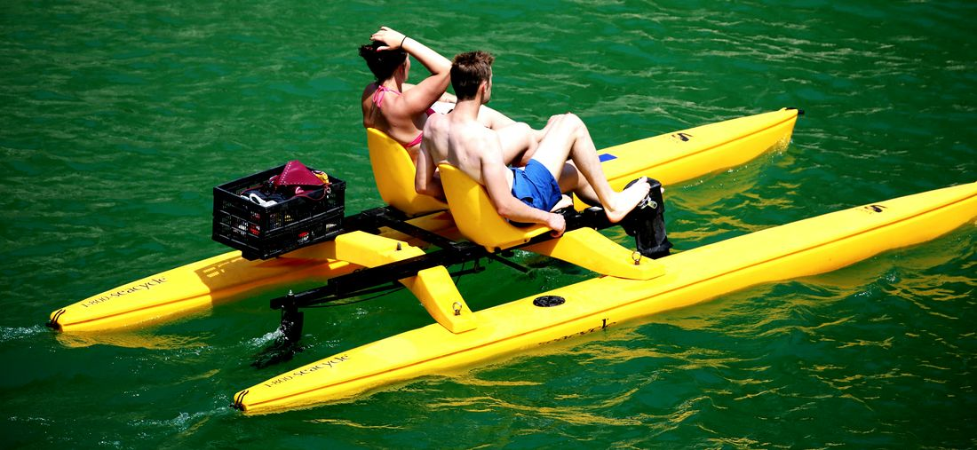 Rear View Of Couple Boating In Calm Water