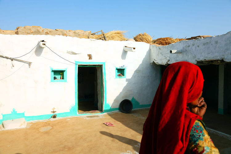 Rear View Of Woman In Traditional Clothing Outside House