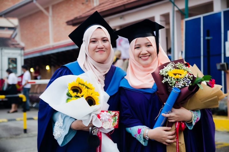 Portrait Of Smiling Female Friends Standing In Graduation Gowns At University