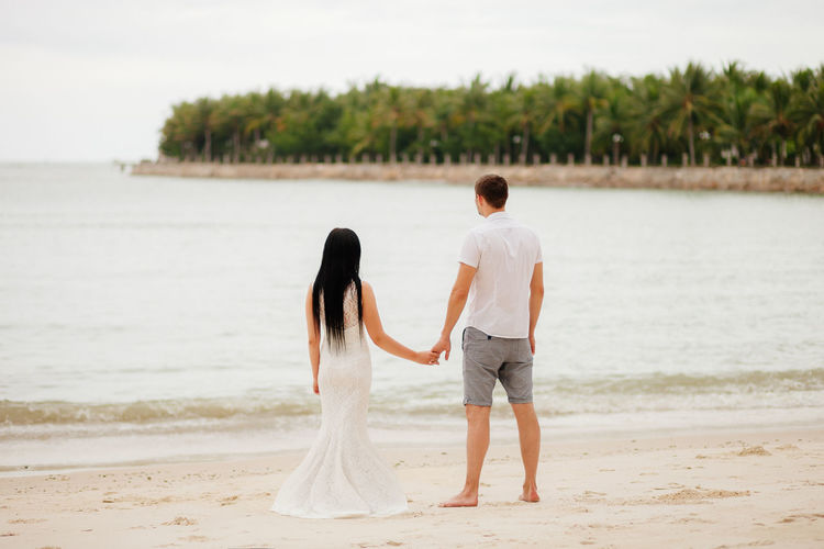 Rear view of couple holding hands while standing on beach