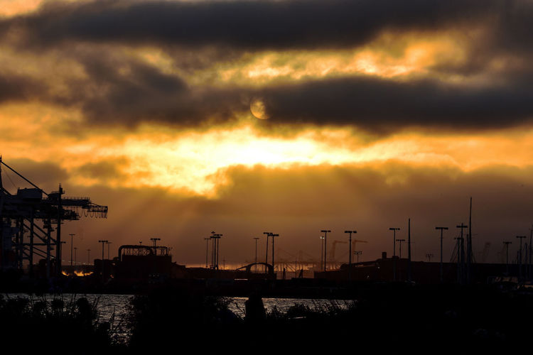 Silhouette cranes against orange sky during sunset