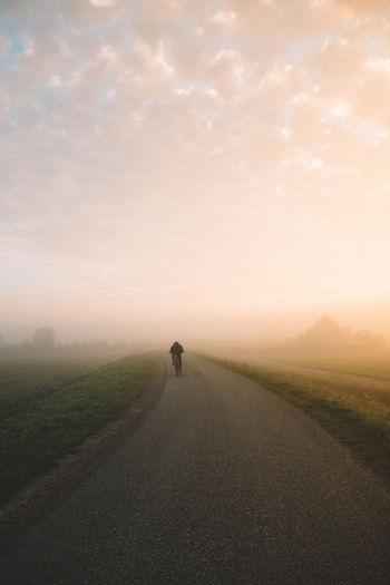 Rear View Of Man Cycling On Road During Foggy Weather Against Sky
