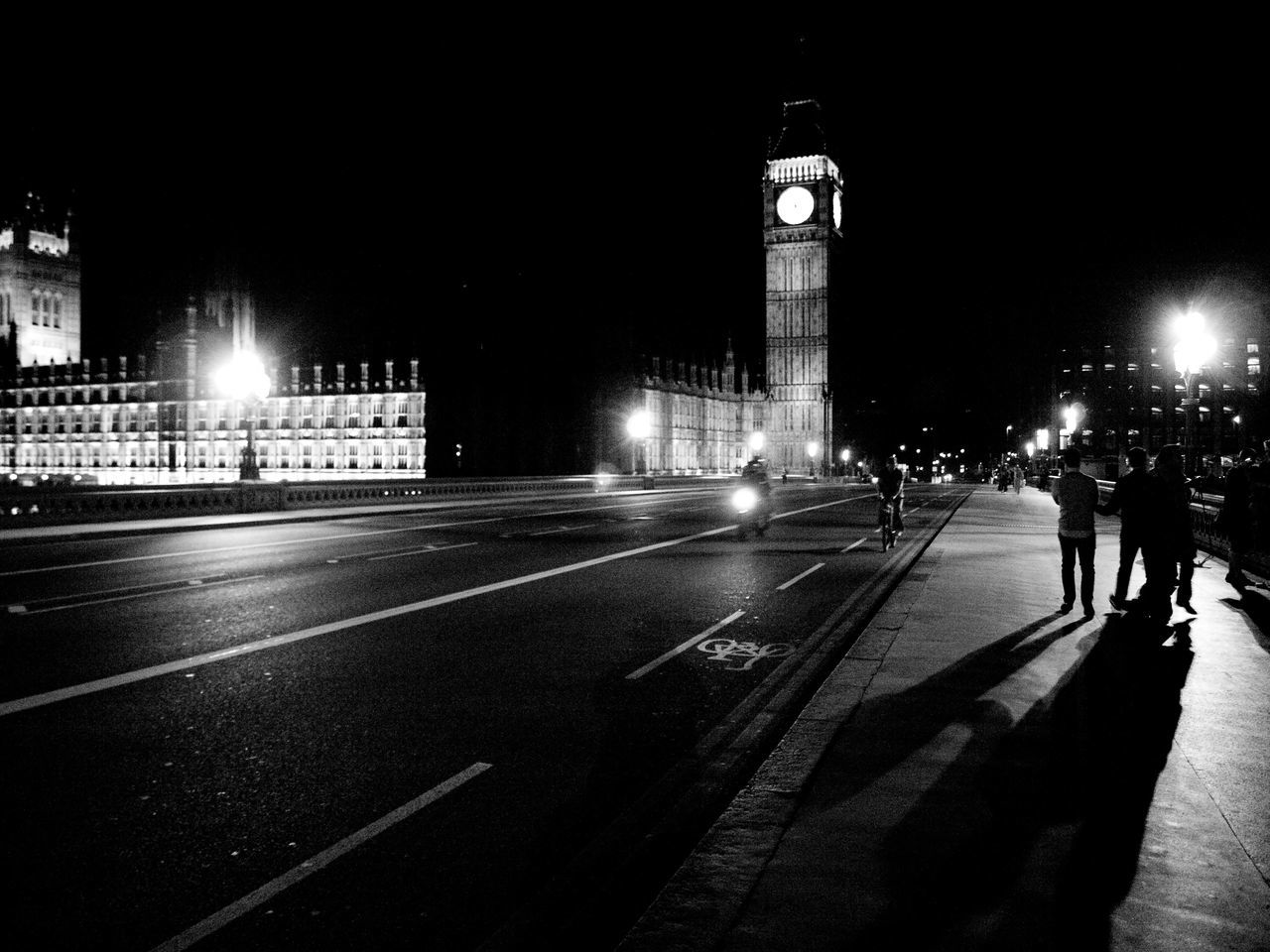 illuminated, night, architecture, built structure, street light, real people, travel destinations, building exterior, travel, road, city life, city, men, outdoors, clock tower, people