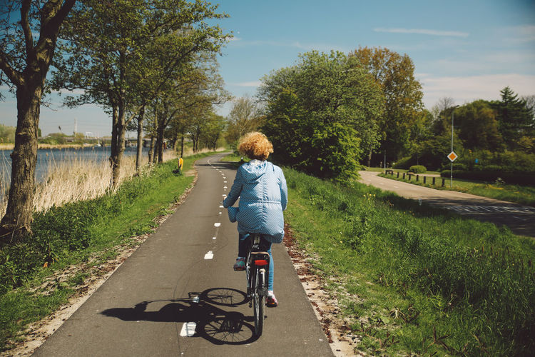 Rear View Of Woman With Curly Hair Riding Bicycle On Road During Sunny Day