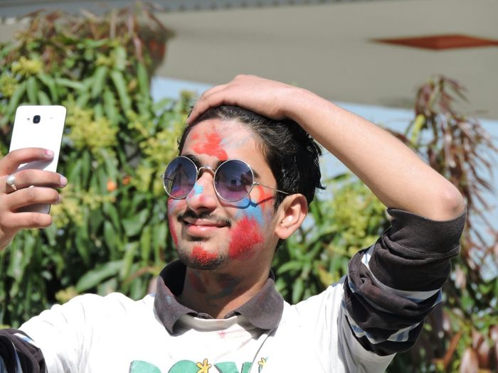 Young man with powder paint on face taking selfie through mobile phone