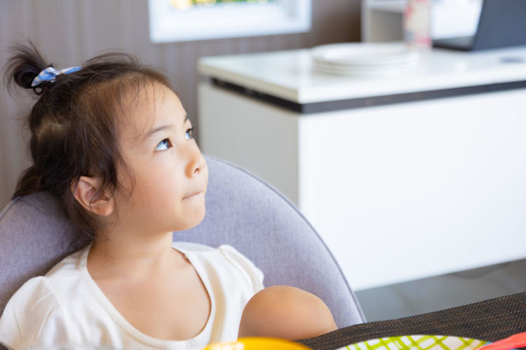 Portrait of cute girl looking at camera at home