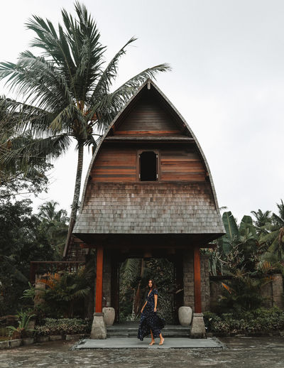 Woman walking on palm tree by building against sky
