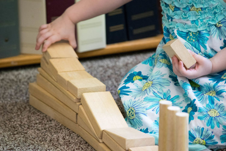 Midsection Of Girl Stacking Wooden Toy Blocks