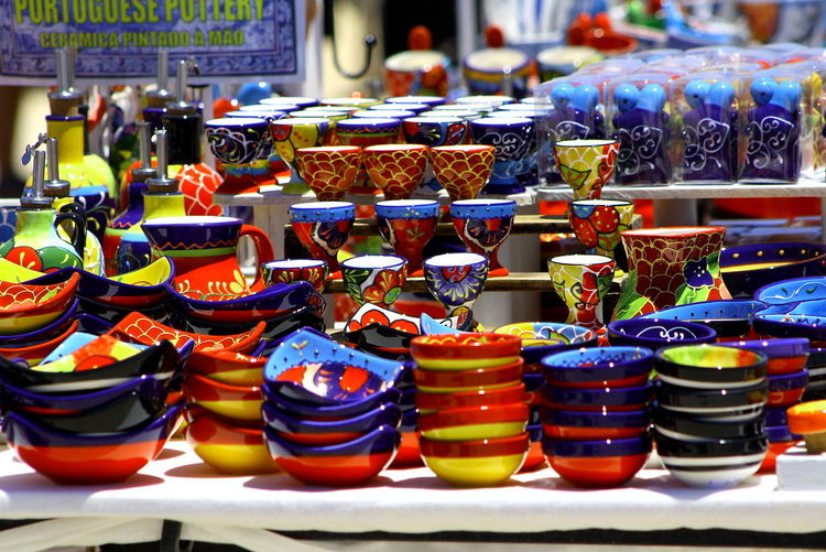 Variety of multi colored kitchen utensils for sale at market