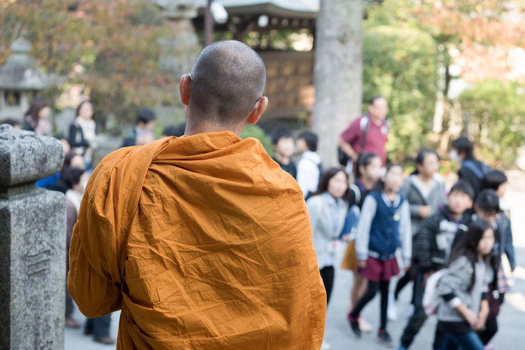 Japanese Buddhist Monk Staring in Silent Contemplation at crowd of tourists. Buddhist Buddhist Temple Japan Monk  People Staring Tourists Yellow Robe