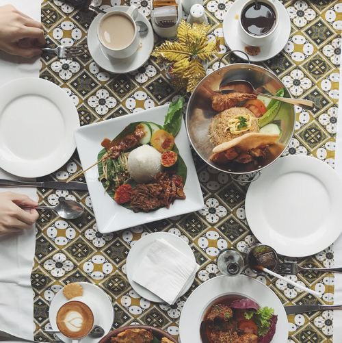 Cropped image of hands with indonesian food at table
