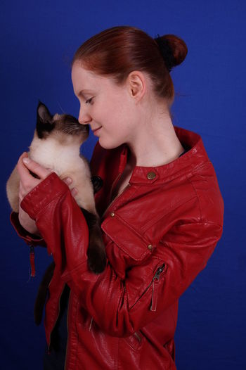 Young woman holding siamese cat against blue background