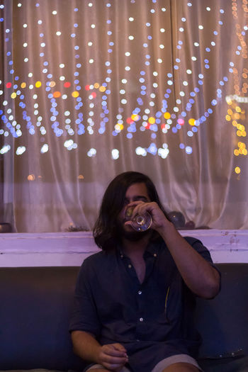Young man drinking red wine at home with with colorful lights in the ceiling.