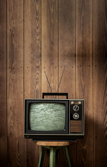 Old television set on stool against wooden wall