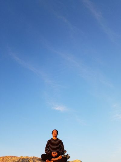 Low Angle View Of Man Meditating On Cliff Against Blue Sky
