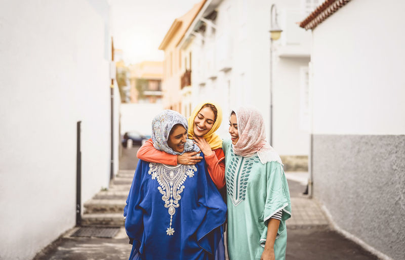 Smiling young woman with friends wearing traditional clothing at alley in city