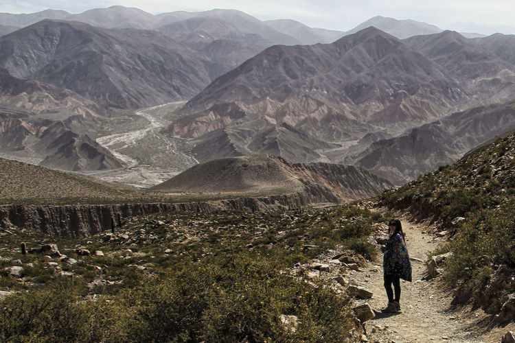 Woman standing on walkway against mountains