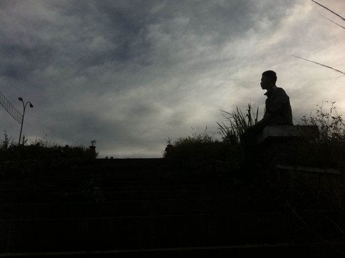 Silhouette of woman sitting against cloudy sky