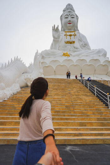 Rear view of woman walking at temple against sky