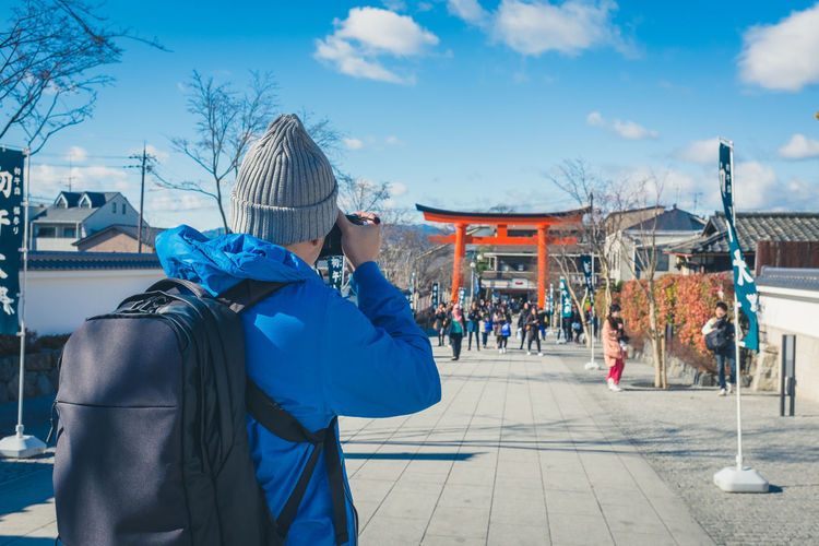 Rear View Of Photographer Photographing People And Torii Gate While Standing On Footpath